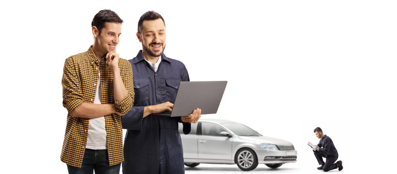 Young male customer and an auto mechanic looking at a laptop computer in a car repair shop
