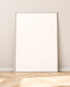 Empty Picture Frame on parquet floor leaning against bright wall. Sunlight flooding in from the left.