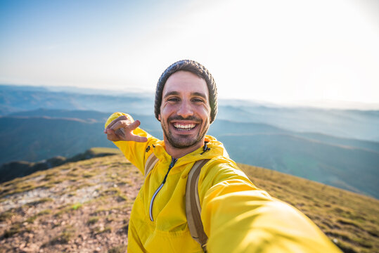 Handsome hiker taking a selfie on the top of the mountain - Happy man with backpack smiling at the camera - Bright filter