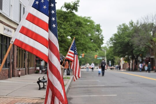 People Walk at at an American Small Town Street Decorated with USA Flags