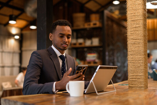 Businessman using laptop and mobile phone at coffee shop