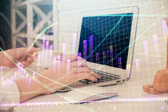 Double exposure of woman hands typing on computer and forex chart hologram drawing. Stock market analysis concept.