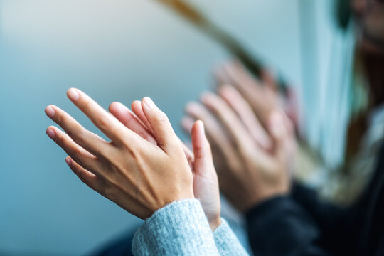 Closeup image of people clapping hands together
