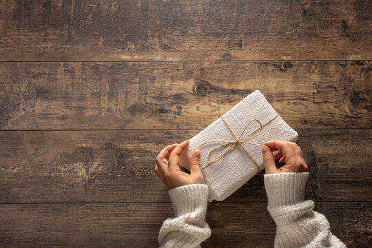 Woman Wrapping Christmas Presents Over Wooden Background. Gift box concept. copy space