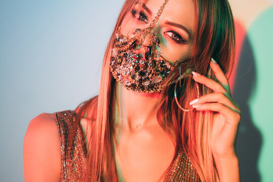 Neon light portrait. Covid-19 fashion. Night club look. Sensual woman in metal chain crystal face mask matching gold outfit posing in pastel green blue red glow.