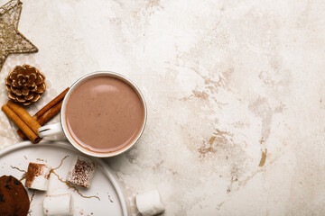 Cup of hot cacao drink with marshmallows on light background