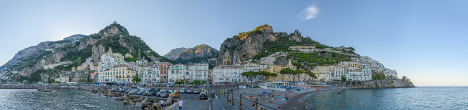 Panorama of Amalfi village in Amalfi Coast, Campany, Italy, from mooring jetty, with old historic town center, beaches and monuments in front of the valley famous for paper mills