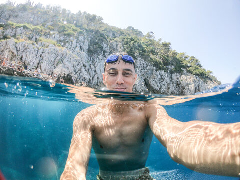 Smiling man swimming in the sea taking a picture of himself.