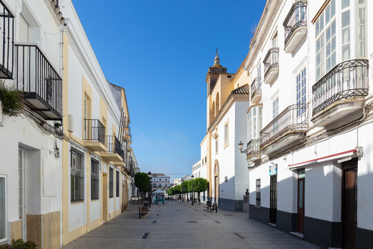 A street in the historic mountain village of Medina-Sidonia in Andalusia in southern Spain with a church and green trees. The houses are all painted white. It's early morning with sunshine.