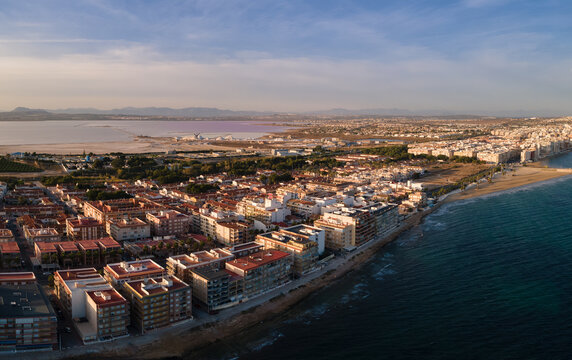 The eastern Spanish city of Torrevieja photographed from the air in autumn. In the background is the lagoon with the salt production. There are some mounds of salt.