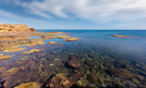 The rocky coast near the eastern Spanish city of Torrevieja in autumn. There is hardly any wind. The water is clear and you can see the sea floor and the stones. A long exposure.