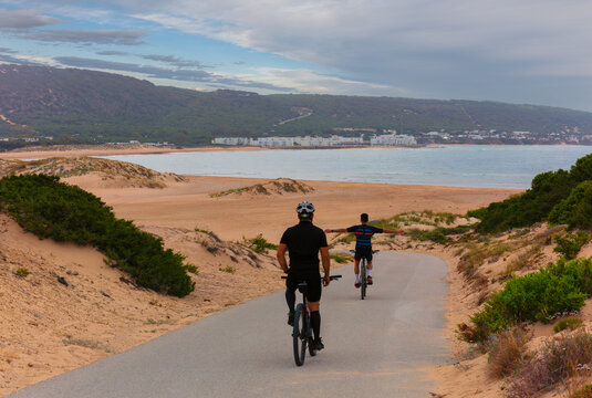 Cyclists on the otherwise deserted Atlantic beach at a camping resort north of Cape Trafalgar during the corona crisis in summer. There are some buildings in the background.