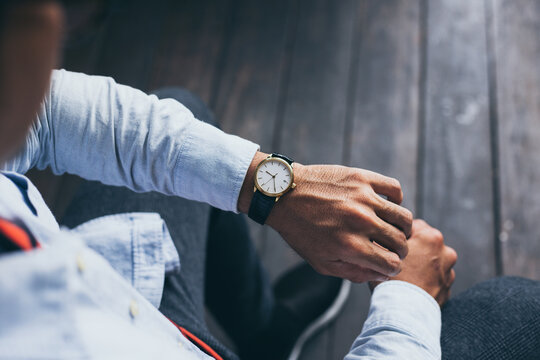 man fashionable wearing stylish looking at luxury watch on hand check the time at workplace.concept for managing time organization working,punctuality,appointment