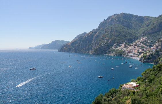 Panoramic view of Amalfi Coast, with Positano seaside village and beach, leisure boats moored in a bay and scenic cliffs from famous hiking path of the Gods in Campany, Italy