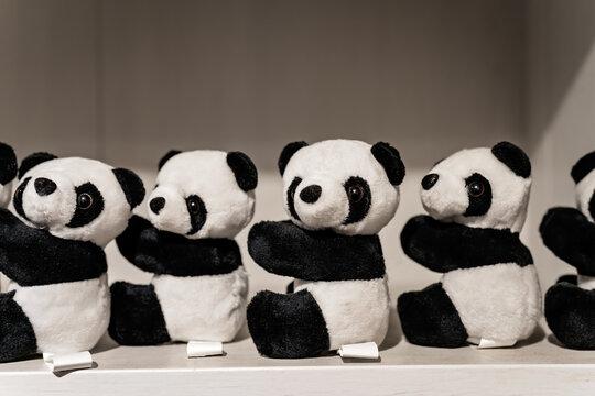 Closeup of stuffed panda toys on a shelf under the lights