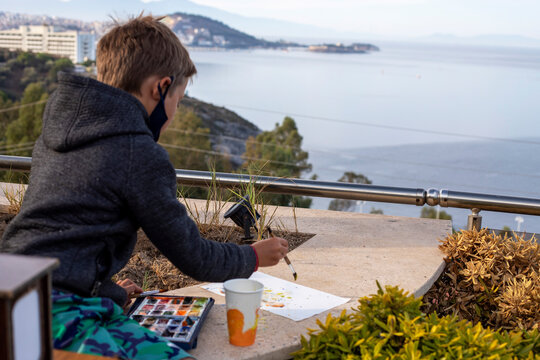 happy boy paints morning landscape with watercolors on a hill, view of Kusadasi, Turkey