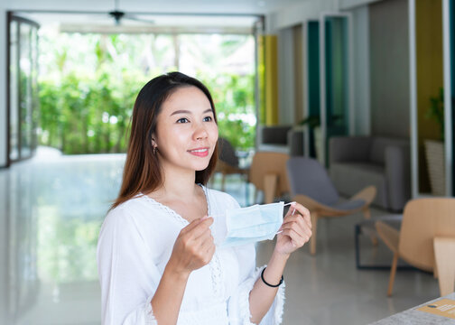 Beautiful young Asian traveler woman holding protective face mask on her hands. New normal, health care, travel and holiday concept