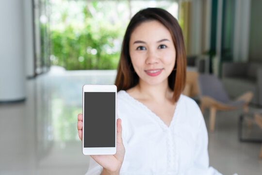 Beautiful young Asian girl holding mobile phone for copy space. Technology and lifestyle concept. closeup