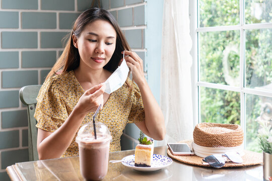 Happy young Asian woman take off medical mask before eating. Health care, new normal lifestyle concept. Closeup