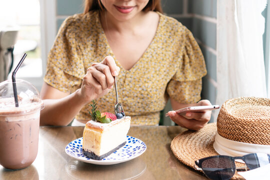 Hands of young Asian woman using mobile phone while eating cake in cafe. Food and beverage, technology and lifestyle concept. Close up