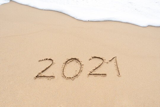 Happy New Year 2021 text on the sandy beach. Welcoming 2021 with new resolutions, dreams concept.