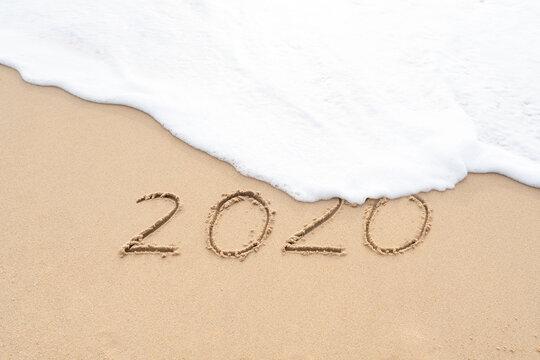 Handwritten 2020 on beautiful sand beach. Goodbye 2020 concept