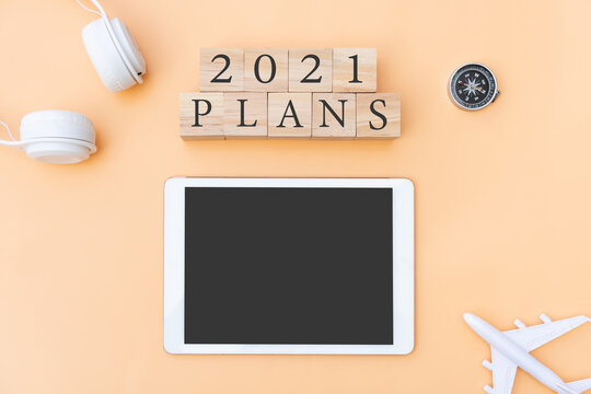 Flat lay of 2021 plans letter on wooden cube with plane, headphone, compass and tablet on beige background. New year planning and traveling concept. Copy space, top view