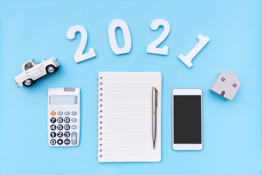 Flat lay notebook, calculator, smartphone, model car and home with number 2021 on blue background. New year goals, Business and finance planing concept. Copy space, top view