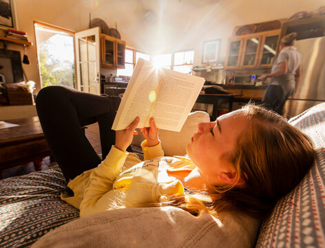 teenage girl reading book at home in early morning light