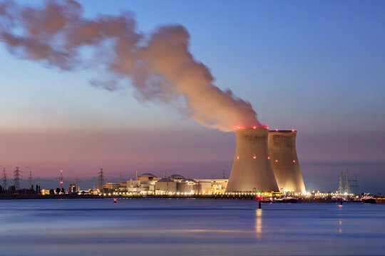 Riverbank with nuclear power plant Doel during a colorful sunset, Port of Antwerp, Belgium