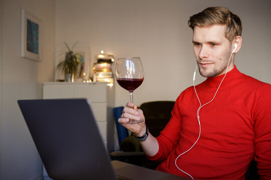 Virtual Christmas Happy hour party. Video conference online meeting with friends and family. Birthday party in online call. Parties during quarantine Long Distance Celebration. Man drinking red wine
