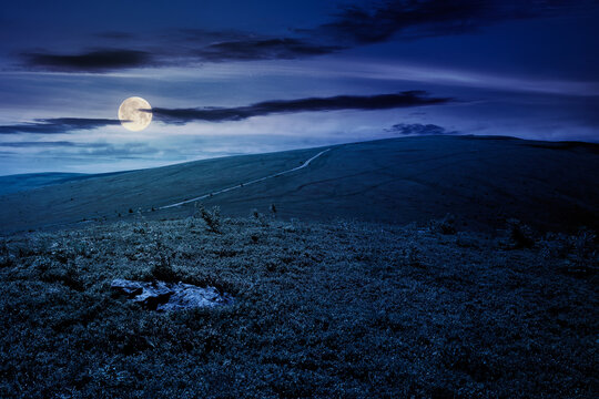 travel carpathian mountains in summer at night. road through green grassy meadows in the distance in full moon light. idyllic landscape with clouds on the blue sky.