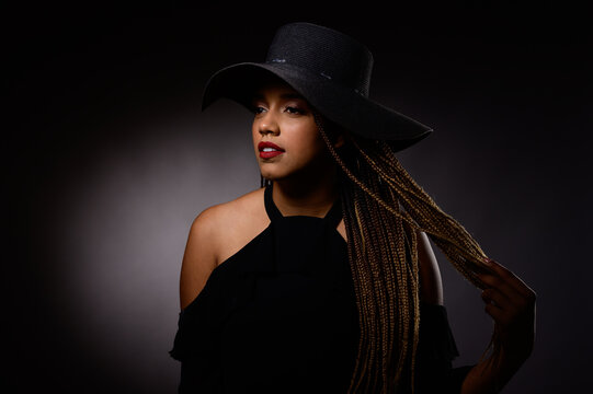 Beauty portrait of a n afro american woman with a hat over dark background black life matter
