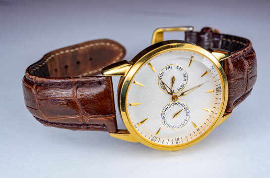 Stylish Gold Watch with slightly worn out brown leather belt