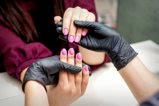 Hands of manicurist holds female fingernails with pink nail polish in nail salon