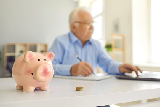 Piggy bank standing on desk with blurred retired man using laptop and doing accounting in background