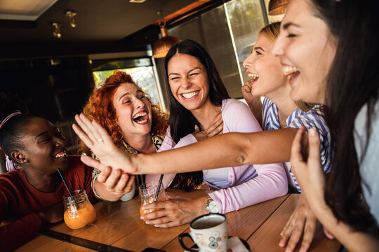 Group of young female friends having fun in coffee shop, her female friends showing engagement ring.