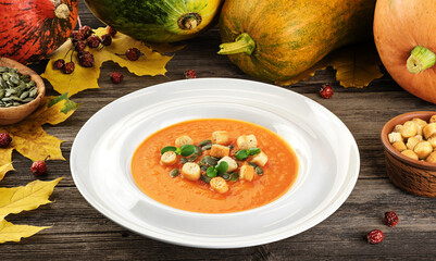 Pumpkin cream soup with croutons and seeds on wooden background.