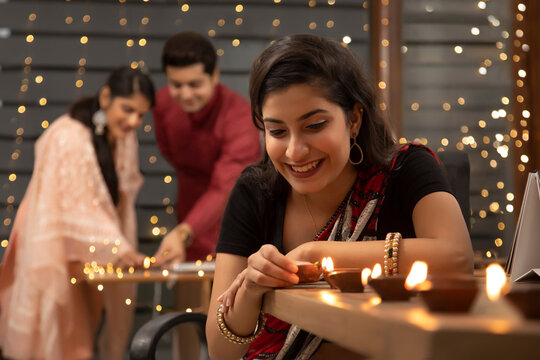 YOUNG WOMAN LIGHTING DIYAS IN OFFICE WITH COLLEGUES IN THE BACKGROUND WITH DIYAS