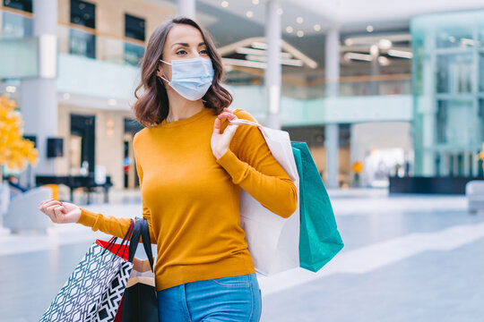 Portrait of casually dressed confident young woman wearing protecting medical mask while walking in mall with bunch of shopping bags in hands