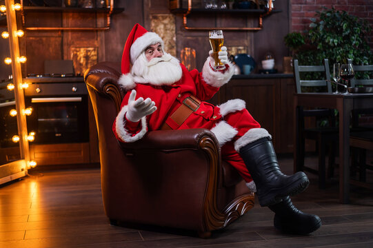 Santa claus with a glass of light beer wishes merry christmas and says toast