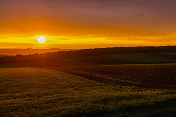 landscape with a sunset over an agricultural field in the autumn