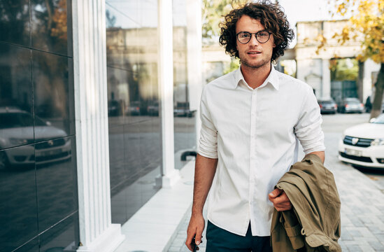 Handsome businessman in eyewear smiling broadly posing outdoors. Male entrepreneur resting in the city street. Smart guy in casual wears spectacles with curly hair walking outside after work