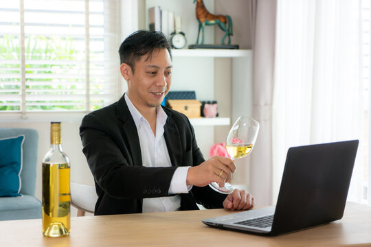 Asian man virtual happy hour meeting party and drinking white grape wine online together with his friend in video conference with digital tablet for a online meeting in video call.