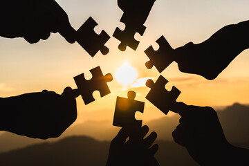 Silhouette  hands connecting  jigsaw puzzle piece against sunrise, Business solutions,  teamwork, partnership, success, goals and strategy concepts. Wall mural