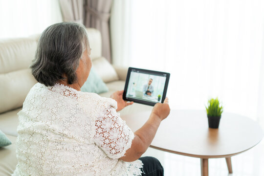 Back view of elderly woman making video call with her doctor with her feeling sick on digital tablet online healthcare digital technology service consultation while staying at home.