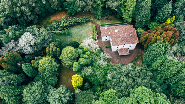Drone aerial view of red roof tile house surrounded by trees