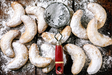 Homemade traditional Christmas shortcrust cookies vanilla crescents with icing sugar and vintage sieve over dark ceramic tile background. Top view