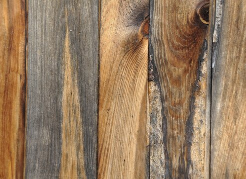 Closeup of a weathered wooden panel with different shaded wood and textures