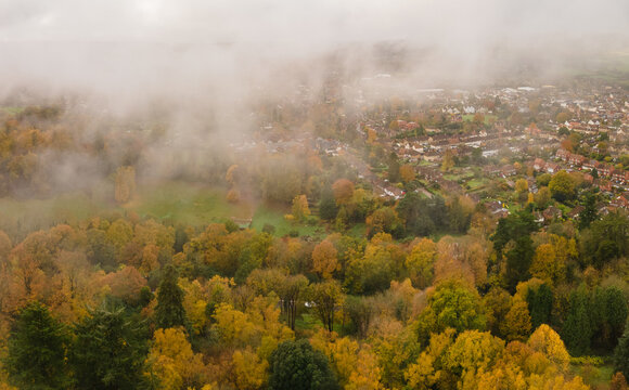 Aerial view of the edge of an English town and beautiful autumn trees with low hanging morning mist